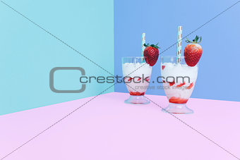 Milkshake with straw and strawberry.