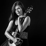 Beautiful young woman holding acoustic guitar