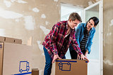 Young couple opening boxes during renovation of new home