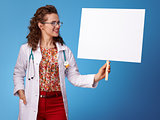 smiling paediatrician woman looking at placard on blue