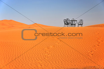 The chair and table stand on the top of the Erg Chebbi dune in Morocco.