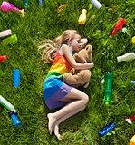 Young girl sleeping with her teddy bear in the plastic littered