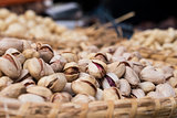 Background of basket of pistachios without shells on market, selective focus
