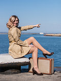 Attractive Young Blonde Woman in Trench with Vintage Suitcase is Sitting on the Jacht Pier and point with a finger in the Sea