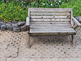 Wooden bench near the flowerbed.
