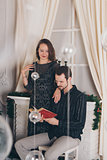 guy and girl reading a book at Christmas by the fireplace