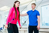 Athlete using workout equipment in gym and getting assistance by trainer
