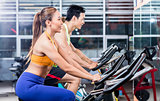 Sportive Asian couple doing indoor cycling in gym