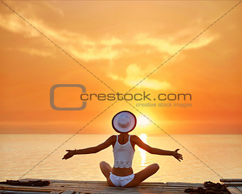 beautiful sexual woman in white hat and bikini on a wooden pier against the sea and sunset