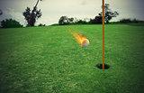 Fiery golf ball near the hole in a grass field