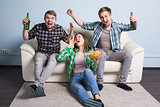 Young friends drink beer and cheering for football
