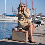 Attractive Young Blonde Woman in Trench with Vintage Suitcase is Sitting on the Jacht Pier