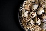 some quail eggs in a black ceramic bowl