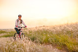 Young Woman Riding Mountain Bikes in the Beautiful Field of Feather Grass at Sunset. Adventure and Travel.
