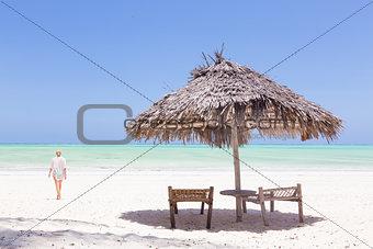 Lady walking to the sea oat white sandy tropical beach of Paje, Zanzibar, Tanzania.