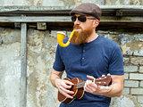 Man with beard playing ukulele and smoking a pipe