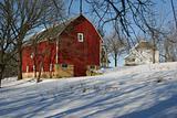 Victorian farmhouse and barn in winter.