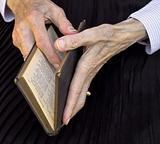 Grandmother reading in an old book of psalms