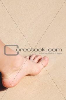 Foot on sandy beach