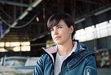 Confident female pilot posing in the hangar