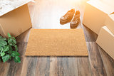 Blank Welcome Mat, Moving Boxes, Shoes and Plant on Hard Wood Fl