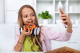 Young teenager girl eating pizza in the kitchen - making a selfi