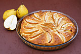 Pie with ripe pears in a glass dish. View from above topview