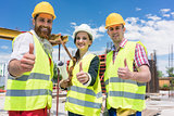 Three colleagues in a construction team showing thumbs up