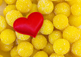 symbol of love family red heart cloth on a background of candied yellow candy balls sweet. base postcard day valentine