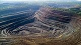 Aerial view of opencast mining quarry with lots of machinery at work. Mining-dressing quarry