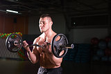 Powerful bodybuilder doing the exercises with barbell. Strong male with naked torso on dark background. Strength and motivation.