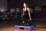 Sporty woman practice on step platform in gym