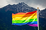 LGBTQ rainbow flag with snowy mountain background view