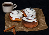 Buns with cinnamon and coffee on parchment paper and a dark background.