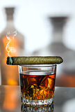 A glass of whiskey and a smoke cigar