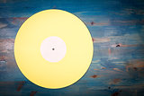 Yellow color vinyl record on blue wooden background
