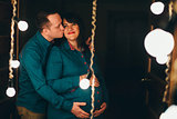 Man hugs his pregnant woman on a lamps background