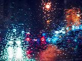 Blurred light traffic lights bokeh with rain drops on glass