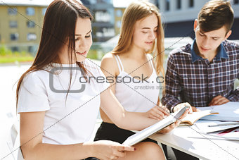 the guy student explains to the girls something and shows in a notebook