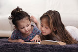 Two Little Sisters Reading Bible on Carpet