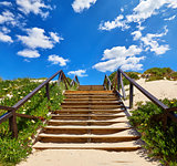 Wooden stairs with railing at beach buried
