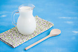 Milk jug napkin wooden spoon blue wooden background.