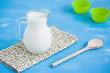 Milk jug napkin wooden spoon blue wooden background.