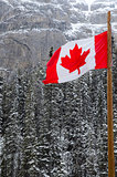 Canadian Flag waving over the mountains of Banff National Park, Canada
