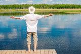 free happy man enjoys the beautiful nature near the lake, view f
