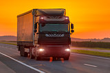 logistics truck on the highway at dawn, orange sky