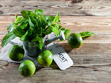 Fresh mint leaves in a vintage watering can and green limes on a wooden background.