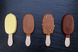 Ice cream on stick covered with chocolate on black slate