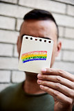 man with a rainbow flag in a piece of paper