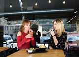 pretty young women drinking in cafe